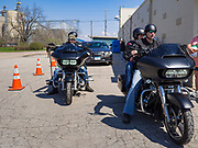 "26 APRIL 2020 - JEWELL, IOWA: Motorcyclists wait to buy ""grab and go"" roast pork dinners in Jewell during a fund raiser Sunday. Jewell, a small community in central Iowa, became a food desert when the only grocery store in town closed in 2019. It served four communities within a 20 mile radius of Jewell. Some of the town's residents are trying to reopen the store, they are selling shares to form a co-op, and they hold regular fund raisers. Sunday, they served 550 ""grab and go"" pork roast dinners. They charged a free will donation for the dinners. Despite the state wide restriction on large gatherings because of the COVID-19 pandemic, the event drew hundreds of people, who stayed in their cars while volunteers wearing masks collected money and brought food out to them. Organizers say they've raised about $180,000 of their $225,000 goal and they hope to open the new grocery store before summer.          PHOTO BY JACK KURTZ"