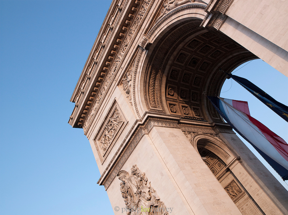 The French national flag hanging from the famous landmark, the Arc De Triomphe, Paris, France