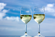 Photographic art of wine glasses against the sky