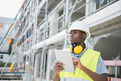 Construction worker holding digital tablet at building site, Munich, Bavaria, Germany
