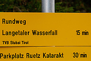 Yellow hiking trail signs, with directions and estimated time to arrive, Stubaital, Tyrol, Austria