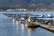 A De Havilland DHC-3 undgoes maintenance with other seaplanes lined up at the Vancouver Harbour Flight Center at Coal Harbour in Vancouver, British Columbia, Canada.  The Vancouver Harbour Flight Centre was previously known as the Vancouver Harbour Water Airport and the Coal Harbour Seaplane Base. North Vancouver and the Seaspan shipyards can be seen in the background.