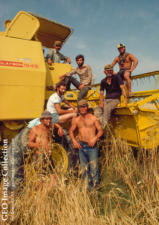 Agricultural workers sit on combine that has supplanted manual labor.