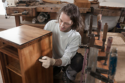 Carpenter French polishing wooden drawer at workshop, Bavaria, Germany