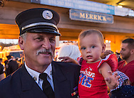 Merrick, NYk, USA. 11th Sept. 2015. RILEY E. GIES, one-year-old granddaughter of Fire Chief Ronnie E Gies who died responding to 9/11 NYC Terrorist Attack, is held by CRAIG MALTZ, a Bellmore volunteer firefighter, after Merrick Memorial Ceremony for Merrick volunteer firefighters and residents who died due to 9/11 terrorist attack at NYC Twin Towers. Ex-Chief Ronnie E. Gies of Merrick F.D. and FDNY Squad 288, and Ex-Captain Brian E. Sweeney, of Merrick F.D. and FDNY Rescue 1, died responding to the attacks on September 11, 2001.