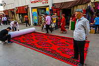 Uyghur men selling carpet in the bazaar, Turpan, Xinjiang Province, China. Turpan is a small oasis town and former Silk Road outpost. Uyghur people are a Central Asian people of Muslim Turkic origin. They are China's largest minority group.