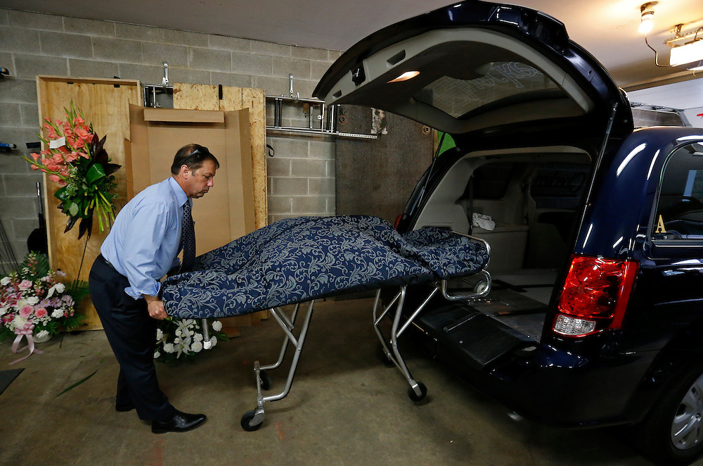 """Glueckert Funeral Home Funeral director John Glueckert removes the remains of an abandoned baby from a hearse that was claimed from the Cook County Medical Examiner's officers in Arlington Heights, Illinois, United States, June 11, 2015. More than a year after he was found dead in a plastic shopping bag on a Chicago sidewalk, Glueckert and a non-profit group """"Rest in His Arms"""" stepped in to provide funeral and burial services for the baby boy. The teenage mother is charged with murder.  REUTERS/Jim Young"""