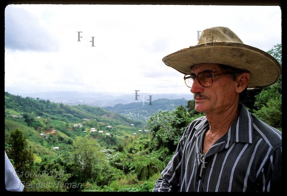 Man in worn canvas cowboy hat gazes @ view from his hilly Caguas suburb called Los Velazquez. Puerto Rico