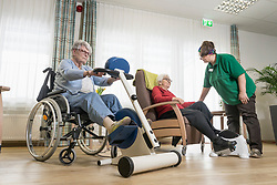 Nurse with senior women exercising on exercise bike in rest home