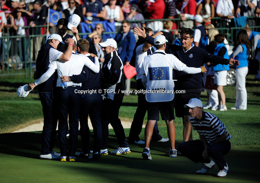 Jim FURYK (USA) squats down in disbelief that he and team USA have lost the Ryder Cup,as from left to right Justin ROSE (EUR),Ian POULTER (EUR),Luke DONALD (EUR) and assistant Paul MCGINLEY (EUR) and caddies celebrate their stunning victory on 18th green during final day Singles,Ryder Cup Matches,Medinah CC,<br /> Medinah,Illinois,USA.