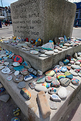 Covid-19 - Stones painted in support of the NHS, placed at the base of the King Alfred commemoration column in Swanage Bay Dorset. Coronavirus lockdown UK May 2020