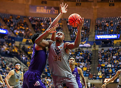 Jan 14, 2020; Morgantown, West Virginia, USA; West Virginia Mountaineers forward Oscar Tshiebwe (34) shoots in the lane while defended by TCU Horned Frogs center Kevin Samuel (21) during the second half at WVU Coliseum. Mandatory Credit: Ben Queen-USA TODAY Sports