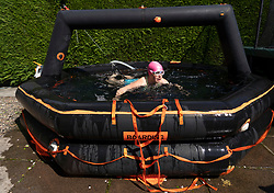 Uphall, Scotland, UK. 25 May 2020. Emily Aston, a wild open water swimmer with the Fife Wild Swimmers group, during a daily dip in her garden pool made from a ship's life raft.  Many wild swimmers have been denied the opportunity to pursue their sport during Covid-19 lockdown and have purchased pools for their gardens to maintain their wellbeing. Iain Masterton/Alamy Live News