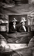 Seaside holiday photograph from Weston-super-Mare, Somerset.  Women posing in a mock up of a ballooning scene set up in the photographer's studio. c1910.