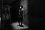 E.F. (18), paciente de tuberculosis, parado en la entrada del edificio donde vive, en el Cerro San Cosme en el distrito de La Victoria (Lima). El 26 de noviembre del 2019 le diagnosticaron la enfermedad en el Hospital de Bravo Chico de El Agustino. E.F. vive junto a su madre, su hermana y sus dos sobrinos en un pequeño cuarto. Su sueldo apenas le alcanza para pagar el alquiler y alimentar a su familia, motivo por el cual muchas veces él deja de comer. Perú. 21 de diciembre del 2019.
