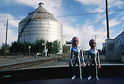 """Alien figures (3"""" tall figure sold as """"The Roswell Alien"""" by Shadowbox Collectibles, Inc.) tour the area around the storage silos by the railroad tracks, downtown Roswell, New Mexico. The figures are actually sitting on the dashboard of the photographer's rental car. (1997)"""