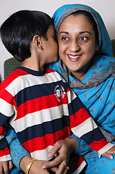 Portrait of young boy whispering to his mother,