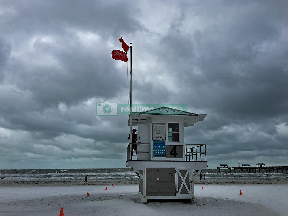 October 7, 2016 - Tampa, Florida, U.S. - The water is closed to the public as a no swimming flag flies off the lifeguard tower on Clearwater Beach. The beach was windy and rough, according to lifeguards, with 35 to 40 miles-per-hour sustained winds and three to five foot seas Friday morning from Hurricane Matthew, which was on the other side of the state. (Credit Image: © Jim Damaske/Tampa Bay Times via ZUMA Wire)