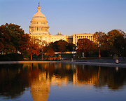 Warm light of sunset illuminating the United States Capitol Building with the reflecting pool in the foreground, Washington, District of Columbia.