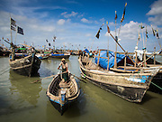 07 NOVEMBER 2014 - SITTWE, RAKHINE, MYANMAR: A boatman rows his lighter to shore in a Rohingya IDP camp near Sittwe. The government of Myanmar has forced more than 140,000 Rohingya Muslims who used to live in Sittwe, Myanmar, into squalid Internal Displaced Person (IDP) camps. The forced relocation took place in 2012 after sectarian violence devastated Rohingya communities in Sittwe and left hundreds dead. None of the camps have electricity and some have been denied access to regular rations for nine months. Conditions for the Rohingya in the camps have fueled an exodus of Rohingya refugees to Malaysia and Thailand. Tens of thousands have put to sea in rickety boats hoping to land in Malaysia but sometimes landing in Thailand. The exodus has fueled the boat building boom on the waterfront near the camps. Authorities expect the pace of refugees fleeing Myanmar to accelerate during the cool season, December through February, when there are fewer storms in the Andaman Sea and Bay of Bengal.   PHOTO BY JACK KURTZ