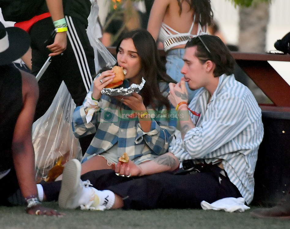 EXCLUSIVE: Brooklyn Beckham and his girlfriend Hana Cross chow down on some food at Coachella. The pair, who were joined by a couple of friends were seen chowing down on some hotdogs at the festival. Brooklyn walked around with his shirt unbuttoned as he held his girlfriend close. 12 Apr 2019 Pictured: Brooklyn Beckham and Hana Cross. Photo credit: Marksman/ Snorlax / MEGA TheMegaAgency.com +1 888 505 6342
