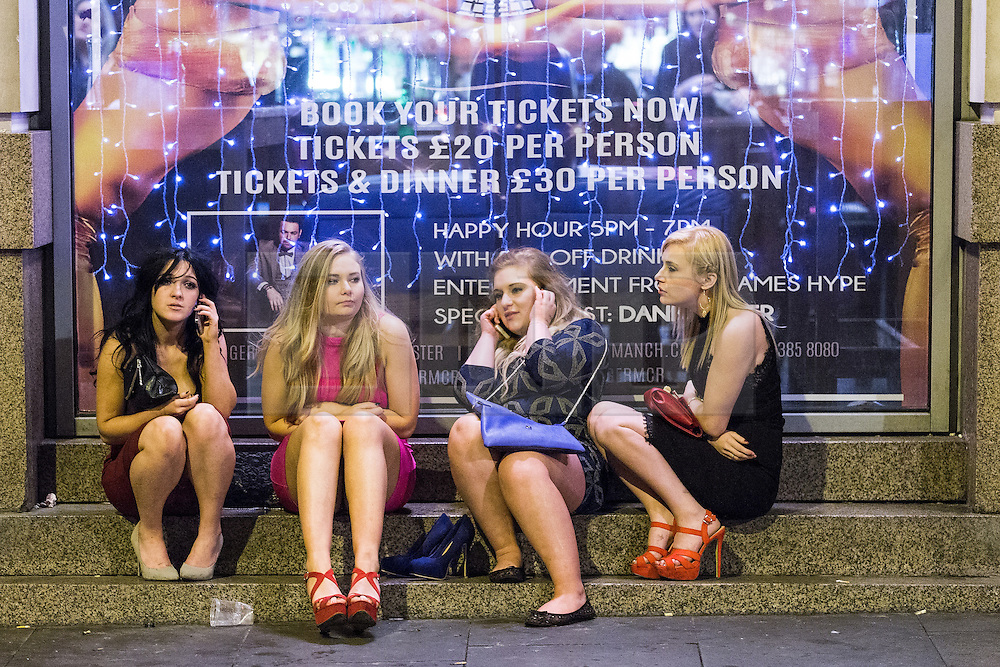 © Licensed to London News Pictures . 01/01/2015 . Manchester , UK . Four women sit on steps outside Tiger Tiger . Revellers usher in the New Year on a night out in Manchester City Centre .  Photo credit : Joel Goodman/LNP