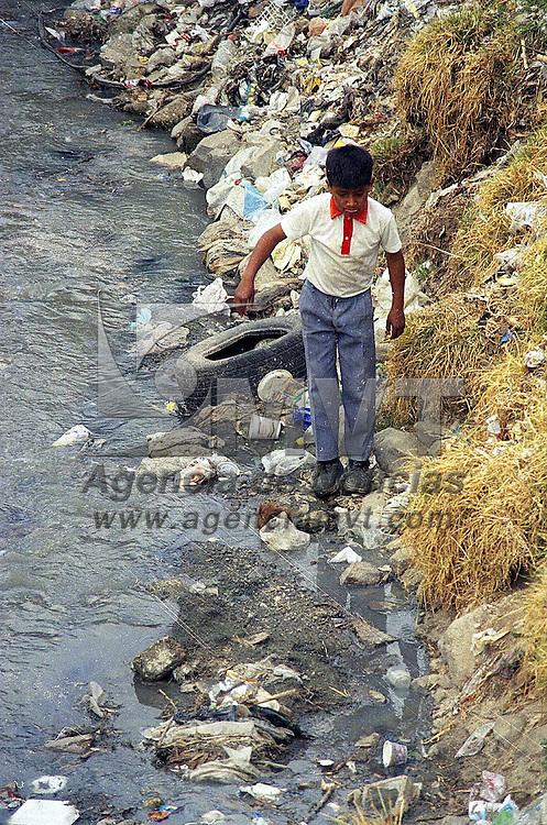 Toluca, Méx.- Un niño camina sobre la basura y desperdicios a un costado del rio verdiguel en la comunidad de San Andres Cuescontitlan. Agencia MVT / H. Vázquez E.