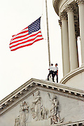 US Capitol lower the flag to half mast following a shooting that killed two July 24, 1998 in Washington, DC. Two US Capitol police officers were killed in the incident, one person wounded and the lone gunmen was wounded and taken into custody.