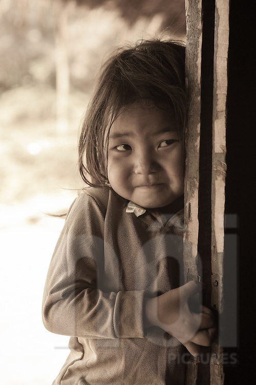 A young Hmong girl timidly peers inside a house full of guests, Than Uyen area, Lai Chau, Vietnam, Southeast Asia
