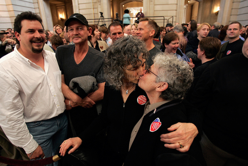 SAN FRANCISCO - FEBRUARY 12: Ellen Pontac (2nd R) and Shelly Bailes who were married one year ago and together for 31 years kiss as Erv Roberts and Terry Price look on.  Gay and Lesbian couples who were married last year attend the 1st wedding anniversary bash hosted by Mayor Gavin Newsom in City Hall on Saturday February 12, 2004. Several thousand couples along with their family and friends attended the morning event which will include celebrations throughout the day.  Photograph by David Paul Morris