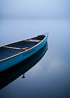 An empty canoe on the shore of a calm lake on a foggy morning just after sunrise.  Kettle Pond, Groton State Forest, Vermont