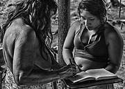 Trois-Sauts, Guyane, 2015.<br /> <br /> En 1946, la départementalisation de la Guyane ne concerne que le littoral. L'intérieur, alors appelé « Territoire de l'Inini », se voit accorder le statut de « nation indépendante sous protectorat ». Ses habitant ne sont pas enregistrés dans les registres de l'état civil et n'ont donc pas les mêmes droits que les guyanais du littoral. Il faut attendre un nouveau découpage administratif de l'ensemble du territoire en 1969, pour que l'intérieur soit intégré au département. Ses habitants noirs marrons et amérindiens vont alors être progressivement « francisés », à mesure que le système administratif pénètre à l'intérieur des terres. Malgré un certain nombre de jugements supplétifs d'acte de naissance, ils sont encore aujourd'hui français, étrangers ou sans état civil.<br /> <br /> Dans le cadre d'une enquête administrative, un gendarme de Camopi qui remplit le rôle d'officier d'état civil recueille le témoignage d'une grand-mère qui atteste de la naissance de son petit fils sur le sol français de Trois-Sauts. L'enfant n'a pas été déclaré à la naissance 25 ans plus tôt, sa mère a accouché seule et son père était trop saoul pour pouvoir se rendre à Camopi et effectuer les démarches nécessaires. Ce complément d'enquête ordonné en janvier 2015 répond à la précédente demande de la famille effectuée en 2010. Ce type de mission a lieu deux à trois fois par an, la difficulté pour les gendarmes en charge du dossier est de pouvoir auditionner des témoins présents au moment de leur passage. <br /> <br /> En 2015, les futures mères suivies par le dispensaire sont systématiquement envoyées à l'hôpital de Cayenne deux mois avant leur terme. Beaucoup préfèrent accoucher plus traditionnellement en forêt pour ne pas quitter leur famille. Les enfants ne sont alors pas toujours déclarés à la naissance.