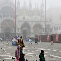 VENICE, ITALY - JANUARY 05:  A woman and two kids feed pigeons in St Mark's Square as thick fog shrouds the city, on January 5, 2012 in Venice, Italy. Venice woke up this morning under a heavy blanket of fog adding magic to the atmosphere of the city.