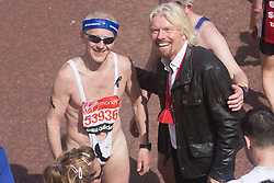 © Licensed to London News Pictures. 21/04/2013. London, England. Picture: Sir Richard Branson greeted many runners who finished personally. Here: with a man in a mankini. Celebrity Runners and Fun Runners finish the Virgin London Marathon 2013 race in the Mall, London. Many wore black ribbons to pay their respect for those who died or were injured in the Boston Marathon. Photo credit: Bettina Strenske/LNP