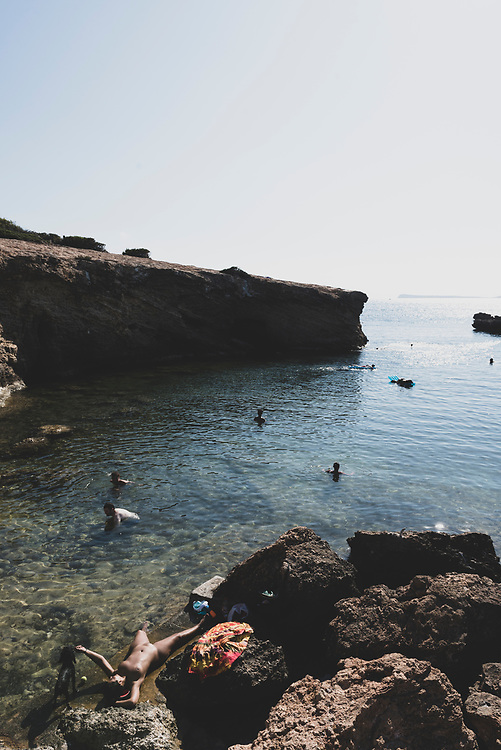 Cala Gració, Ibiza, Spain - July 30, 2018: A nude sunbather reaches up to pet a dog at the rocky beach at Cala Gració, Ibiza, Spain.