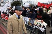 An English gentleman passes Libyan exiles opposite their London embassy during the Gaddafi uprising. Holding placards and banners that show some atrocities carried out by mercenaries and the army, they shout for regime change and for Colonel Gaddafi to be hanged for war crimes, the elderly man carefully passes their railing enclosure without looking them in the eye. Further along the railings, Islamic extremist demand Shariah law after the Gaddafi uprising. Holding up his placards that ask for Allah's Holy law and a Shariah way of life for Libya and that Democracy is the path to Hellfire