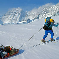 ANTARCTICA, Mount Vinson Expedition. Dr. Lis Densmore (MR) pulls a heavy sled to Camp One, en route to becoming first woman to climb continent's 16 058-foot highest mountain. 15,918-foot Mount Tyree (third highest) is in background.  Ellsworth Mountains.