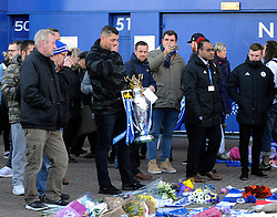 A supporter holds a replica of the Premier League trophy outside Leicester City Football Club after a helicopter crashed Saturday killing Leicester City's owner, Thai billionaire Vichai Srivaddhanaprabha and four other people, in Leicester, England, Monday Oct. 29 2018. The helicopter crashed in flames in a car park next to the soccer club's stadium shortly after it took off from the pitch following a Premier League game on Saturday night. (AP Photo/Rui Vieira)