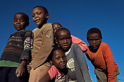 A group of children pose for a photograph in Leribe, Lesotho. An estimated 12 million children under the age of 17 (just under 10% of children) living in sub-Saharan Africa have lost one or both parents to AIDS.