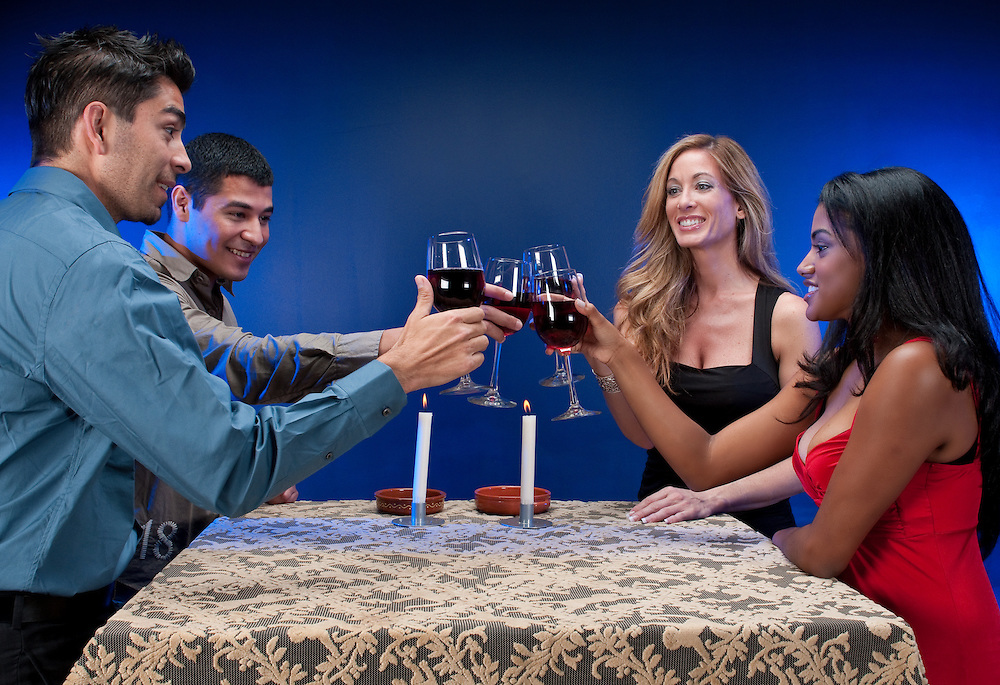 Group of mixed races friends toasting in night club or restaurant.