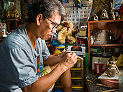 30 JULY 2016 - BANGKOK, THAILAND: LEK, an artisan who makes clay figurines works in his home workshop in the Pom Mahakan Fort slum. He said his family has been in the neighborhood for more than 40 years and can't move because if he moves his customers, mostly Thai and foreign tourists, won't be able to find him. Mahakan Fort was built in 1783 during the reign of Siamese King Rama I. It was one of 14 fortresses designed to protect Bangkok from foreign invaders. Only of two are remaining, the others have been torn down. A community developed in the fort when people started building houses and moving into it during the reign of King Rama V (1868-1910). The land was expropriated by Bangkok city government in 1992, but the people living in the fort refused to move. In 2004 courts ruled against the residents and said the city could take the land. Eviction notices have been posted in the community and people given until April 30 to leave, but most residents have removed to move. Residents think Bangkok city officials will start evictions around August 15, but there has not been any official word from the city.      PHOTO BY JACK KURTZ