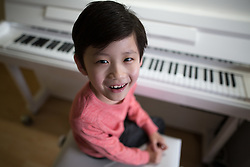 © Licensed to London News Pictures . 24/05/2015 . Manchester , UK . Pianist LEO BAILEY-YANG (seven) (correct) (pictured in his home in Clayton , East Manchester) appeared on Britain's Got Talent and is one of the youngest people ever to have passed Grade 8 Piano with distinction . Photo credit : Joel Goodman/LNP