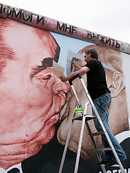 Russian artist Dmitry Vrubel repainting his famous  original mural of Brezhnev kissing Honecker on the Berlin Wall at the East Side Gallery in Berlin in June 2009