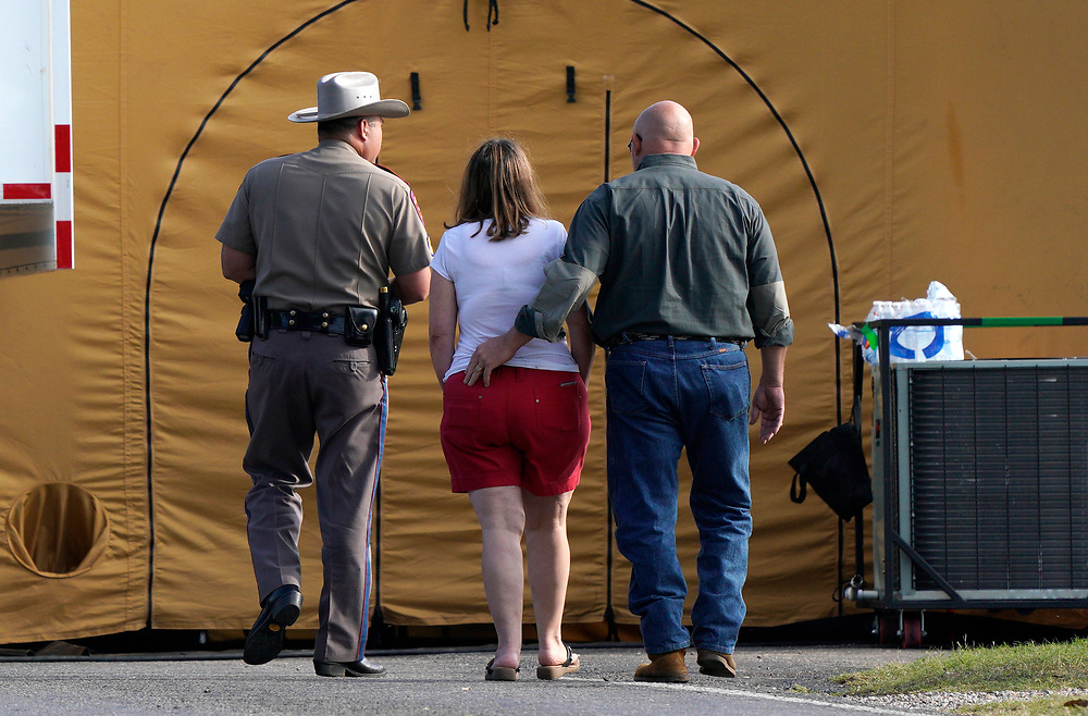 A woman is escorted to site of a shooting at the First Baptist Church of Sutherland Springs, Texas U.S. November 6, 2017.  REUTERS/Rick Wilking