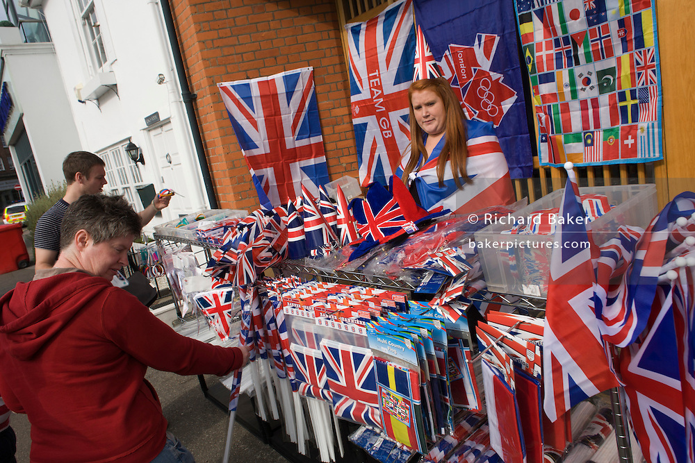 Spectators choose flags to but at an official Olympic merchandise stall on the first day of competition of the London 2012 Olympic 250km mens' road race. Starting from central London and passing the capital's famous landmarks before heading out into rural England to the gruelling Box Hill in the county of Surrey. Local southwest Londoners lined the route hoping for British favourite Mark Cavendish to win Team GB first medal but were eventually disappointed when Kazakhstan's Alexandre Vinokourov eventually won gold.