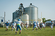 COLFAX, ND - The Richland Colts varsity football team practices on the school field across the street from the Colfax Farmers Elevator in Colfax, North Dakota, August 15, 2018. The elevator owned by a group of several dozen local farmers and sells and stores locally-produced grains.