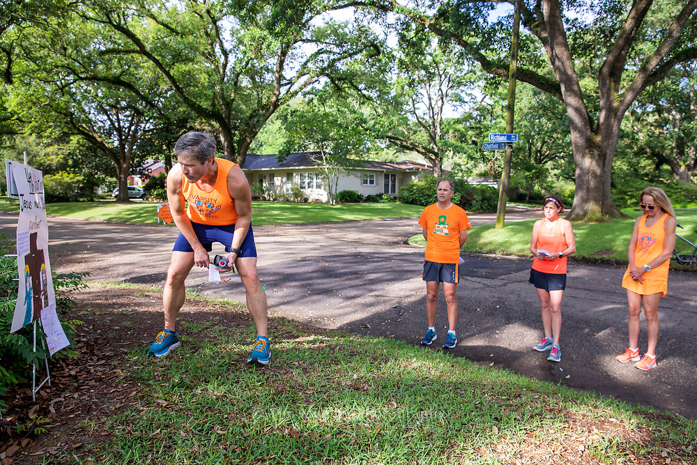 Varisty Sports runner Jason Cashio, left, stops at the fourth station while running the Stations of the Cross in the Webb Park neighborhood. With churches closed because of COVID-19 many neighborhoods in the Baton Rouge area have organized Stations of the Cross for Good Friday. Marked with simple, homemade signs people can view and pray by car, bike, golf cart or on foot the stations displayed in area front yards.