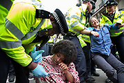 Police speak to one protester as they arrest and remove another as they try to clear climate change activists from the Extinction Rebellion group at Oxford Street near to the Marble Arch camp in protest that the government is not doing enough to avoid catastrophic climate change and to demand the government take radical action to save the planet, on 24th April 2019 in London, England, United Kingdom. Extinction Rebellion is a climate change group started in 2018 and has gained a huge following of people committed to peaceful protests.