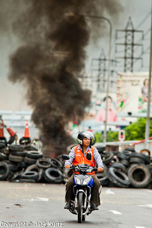 16 MAY 2010 - BANGKOK, THAILAND: A motorcycle taxi looks for fares in front of a burning tire barricade on Rama IV Road Sunday. Thai troops and anti government protesters clashed on Rama IV Road again Sunday afternoon in a series of running battles. Troops fired into the air and unidentified snipers shot at pedestrians on the sidewalks. At one point Sunday the government said it was going to impose a curfew only to rescind the announcement hours later. The situation in Bangkok continues to deteriorate as protests spread beyond the area of the Red Shirts stage at Ratchaprasong Intersection. Many protests now involve people who have not been active in the Red Shirt protests and live in the vicinity of Khlong Toei slum and Rama IV Road. Red Shirt leaders have called for a cease fire, but the government indicated that it is going to go ahead with operations to isolate the Red Shirt camp and clear the streets.      PHOTO BY JACK KURTZ