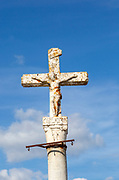 Close up of historic cross crucifixion of Jesus Christ  monument in medieval village with the Latin word oblatus,  Mértola, Baixo Alentejo, Portugal, Southern Europe against blue sky with copy space